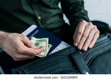 cropped shot of businessman putting passport, ticket and money into suitcase