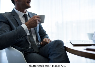 Cropped shot of businessman sitting in office lobby and drinking coffee. Entrepreneur having coffee in office.