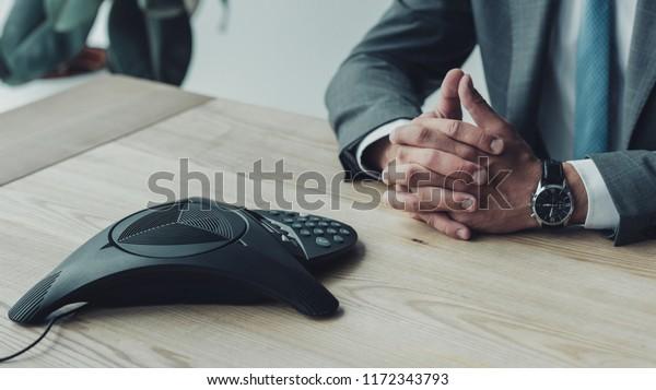 beschnittene Aufnahme von Geschäftsleuten am Arbeitsplatz mit Konferenztelefon