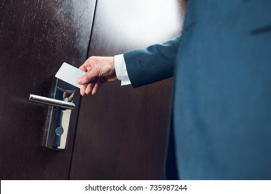 Cropped shot of businessman in suit opening a hotel room door with card
