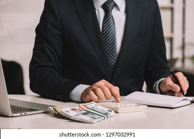 cropped shot of businessman using calculator and taking notes in notepad at workplace with laptop and russian rubles banknotes