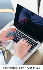 cropped shot of businessman using laptop with blank screen