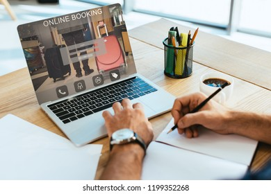 cropped shot of businessman working at tabletop with notebook and laptop with online booking lettering on screen