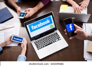Cropped shot of businesspeople using digital devices with facebook logo icons on screens