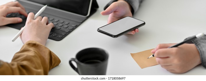 Cropped shot of businesspeople working on tablet and writing an idea on notepad while looking information on mock-up smartphone