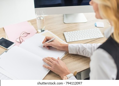 cropped shot of businesswoman doing paperwork at workplace