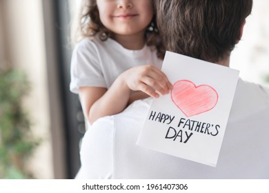 Cropped shot of a cheerful small kid daughter holding greeting card for her father to congratulate him with father`s day, make him surprise and gift. Fatherhood. I love you, dad!