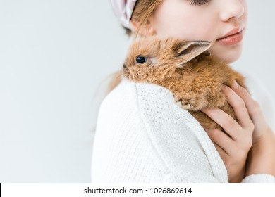 cropped shot of child holding cute furry rabbit isolated on white