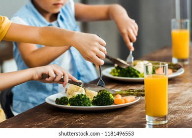 cropped shot of children eating healthy vegetables at wooden table