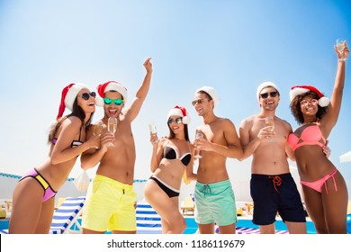 Cropped shot of chilling, dancing international youth in santa`s hats, enjoying on resort beach pool sunny disco, in diverse trendy fashionable bikinies, spectacles, with drinks celebrating christmas