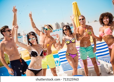 Cropped shot of chilling, dancing international youth, enjoying on resort beach pool sunny disco, in diverse trendy fashionable bikinies, spectacles, caps, with drinks, celebrating holiday