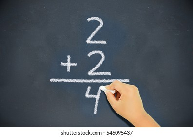 Cropped shot of a class with a child on the board making a simple mathematical equation. two plus two equals four