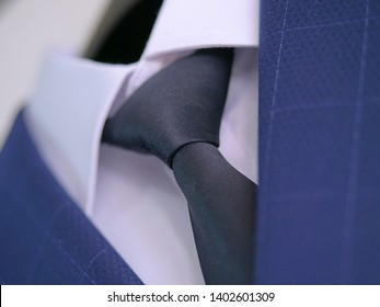 Cropped shot of classy navy blue suit with white shirt and embroidered silk necktie, male accessories for formal attire, elegant groom ensemble, sophisticated businessman or outfit for a job interview