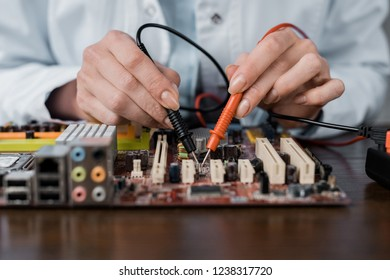 cropped shot of computer engineer with tester examining motherboard