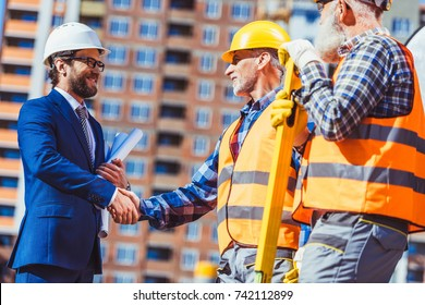 Cropped shot of construction worker in reflective vest shaking hands with businessman wearing hardhat