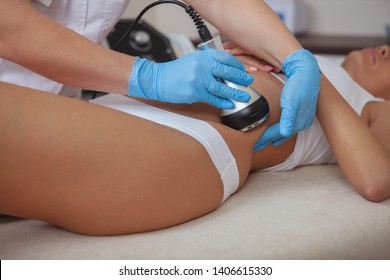 Cropped shot of a cosmetologist doing ultrasound cavitation procedure on the belly of a female client. Unrecognizable woman getting anti-fat treatment at beauty salon. Abdominal slimming concept