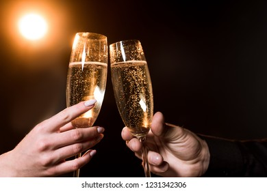 cropped shot of couple clinking glasses of champagne under golden light on black