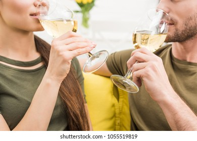 cropped shot of couple drinking wine together on couch at home