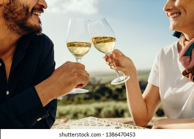 Cropped shot of a couple sitting together with glasses of white wine on a wine date. Side view of a couple on a date talking to each other toasting glass of wine.