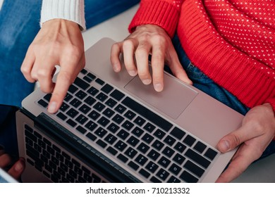 cropped shot of couple in sweaters using laptop