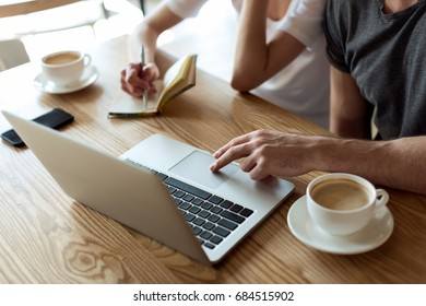 cropped shot of couple working together on laptop in cafe