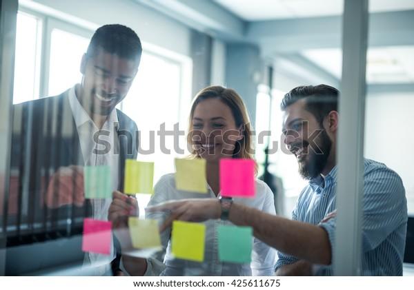 Imagen recortada de compañeros de trabajo usando notas pegajosas en una pared de vidrio durante una reunión.