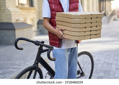 Cropped shot of a delivery man holding boxes with pizza while st