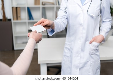 Cropped shot of doctor giving blank business card to patient
