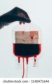 cropped shot of doctor holding plastic bag of blood for transfusion isolated on white