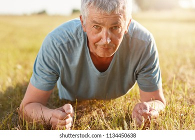 Cropped shot of elderly male in his 50s makes push ups on green grasss while recreats on nature, doesn`t forget about sport, has serious expression. People, determination and motivation concept