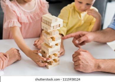 cropped shot of family with two children building tower from wooden blocks at home