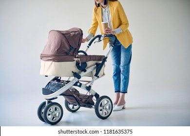 cropped shot of fashionable woman holding disposable coffee cup and standing with baby carriage on grey