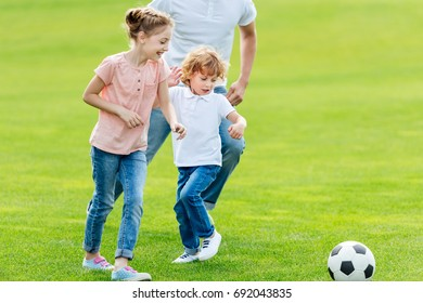 cropped shot of father with happy kids playing soccer in park
