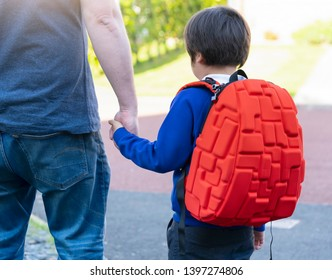 Cropped shot of Father and Son holding hands together, Cheerful schoolboy wearing uniform carrying backpack walking to school, Parent and pupil of primary going to school, First day back to school
