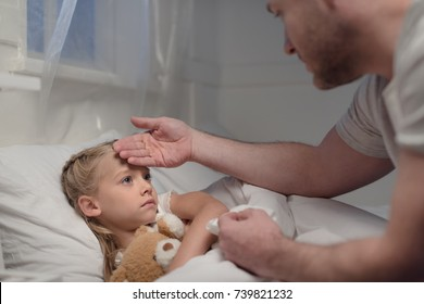 cropped shot of father touching forehead of sick daughter lying in bed