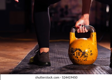 Cropped shot of female athlete exercising with kettle bell. Young sporty woman doing workout in gym.