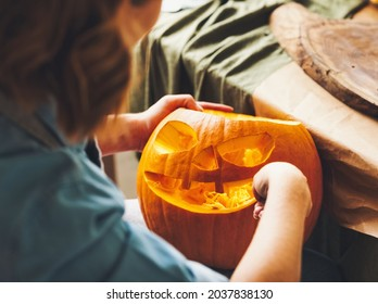 Cropped shot of female carving large orange pumpkin for Halloween party while sitting at wooden table at home, making scary face on jack-o-lantern with knife to set the mood for trick-or-treaters
