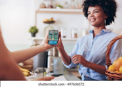 Cropped shot of a female customer paying for her juice by credit card at juice bar. Focus on woman hands holding credit card reader.