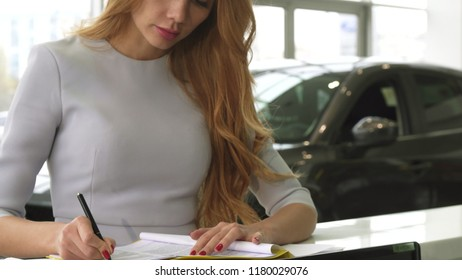 Cropped shot of a female customer signing papers at the dealership showroom