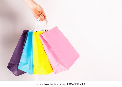 Cropped shot of female hand holding bunch of different colorful blank shopping bags over isolated white background. Many packets with in woman's arms. Black friday sale concept. Copy space, close up.