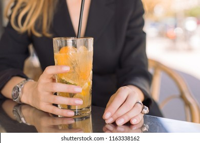 Cropped shot of female hands holding fresh citrus lemonade in glass. Summer iced cocktail on the table outdoors.