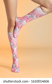 Cropped shot of female legs in dense pink knee socks with childish print of unicorns and rainbows. The photo is made on the sandy yellow background.
