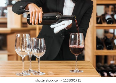 cropped shot of female wine steward pouring wine into glasses at wine store
