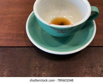 cropped shot of a finished light green cup of hot coffee with red lipstick mark putted on dark brown wooden board table in cafe, coffee lover concept