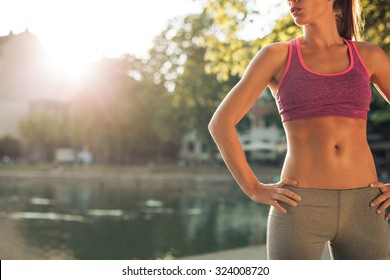 Cropped shot of fit young woman in sportswear standing with her hands on hips outdoors. Female runner ready for a run with sun flare.
