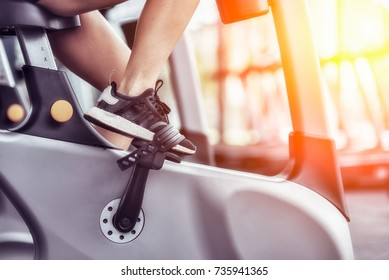 Cropped shot of fitness woman working out on exercise bike at the gym. Female exercising on bicycle in health club, focus on legs.