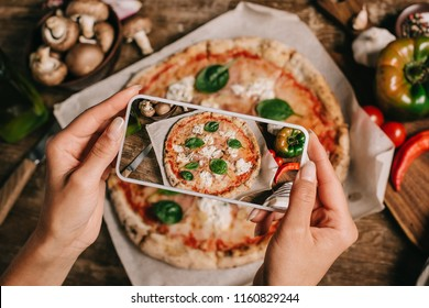 Cropped shot of food blogger taking picture of cooked pizza on baking paper on wooden surface