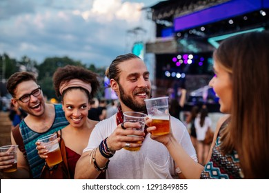Cropped shot of four friends cheering with drinks at a music festival