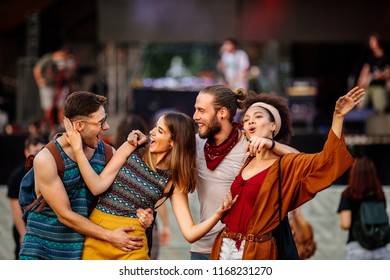 Cropped shot of four friends dancing at a music festival