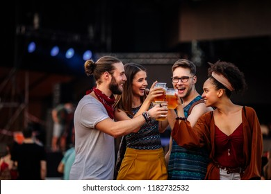 Cropped shot of four friends drinking beer and dancing at a music festival